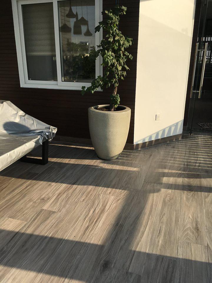 Với các sân thượng có mái che, sàn gỗ hoặc các loại gạch tông màu nâu vàng là lựa chọn khá sáng suốt.