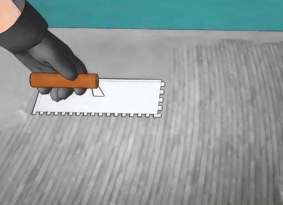 Phết một lớp keo dán gạch lên mặt sàn bằng bay răng cưa
